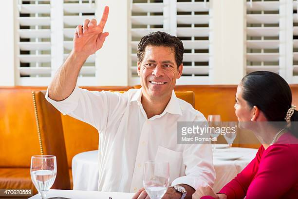 Couple calling waiter at restaurant
