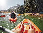Couple canoeing in the lake on a summer day. Man and woman in two different kayaks in the lake on a sunny day.