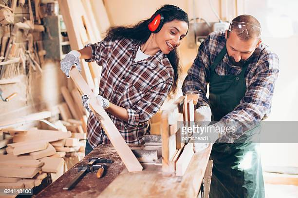 Couple carpenters working at workshop