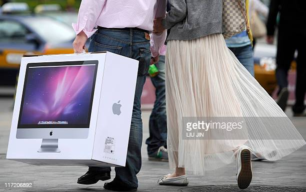 A couple carries a new Mac desktop just bought from the Apple store in Beijing on May 8 2011 Four people were taken to hospital and a glass door...