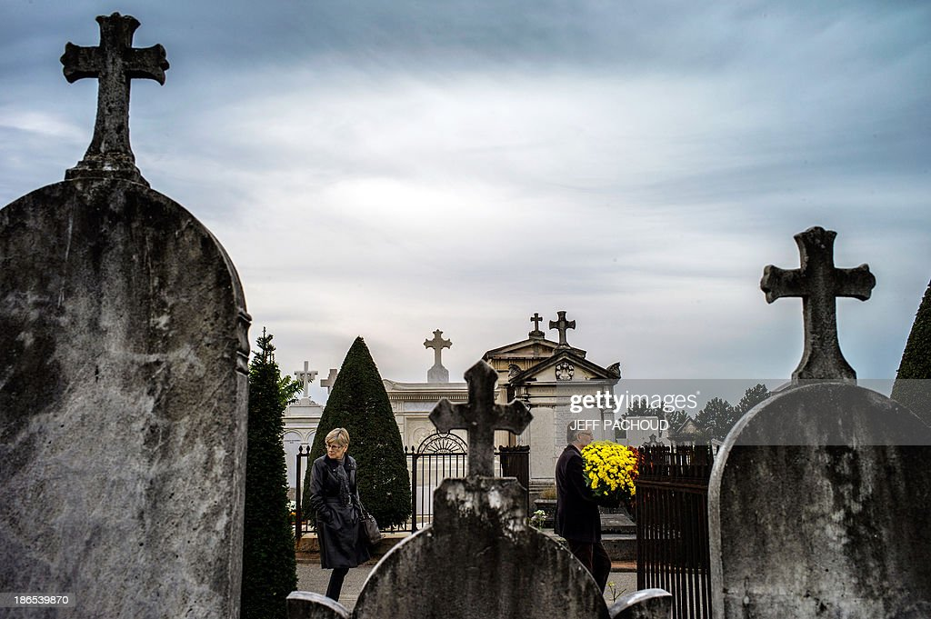 A couple carries a pot of chrysanthemums on November 1, 2013 into a cemetery in the central French city of Lyon, during the All-Saints Day. In France, people place chrysanthemums on graves to mark All-Saints Day on November 1. AFP PHOTO / JEFF PACHOUD