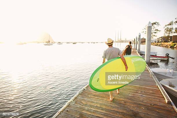 Couple carry paddle-boards along pier, at marina