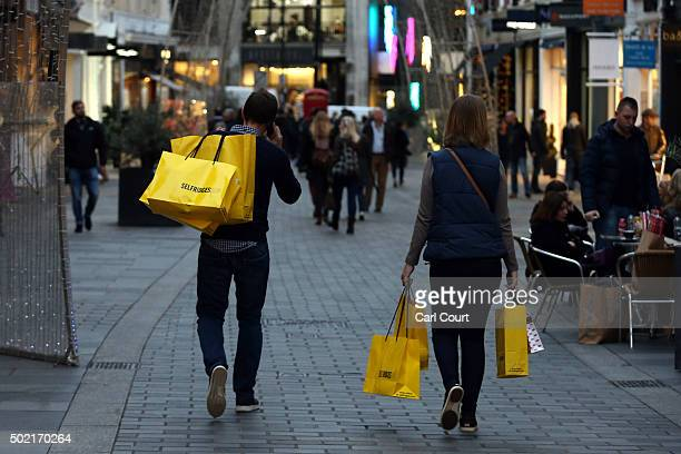 A couple carry Selfridges shopping bags on December 16 2015 in London England Retail Sales for November 2015 have increased by 17% credited to...
