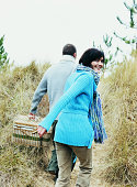 Couple Carrying a Hamper on the Path to a Beach