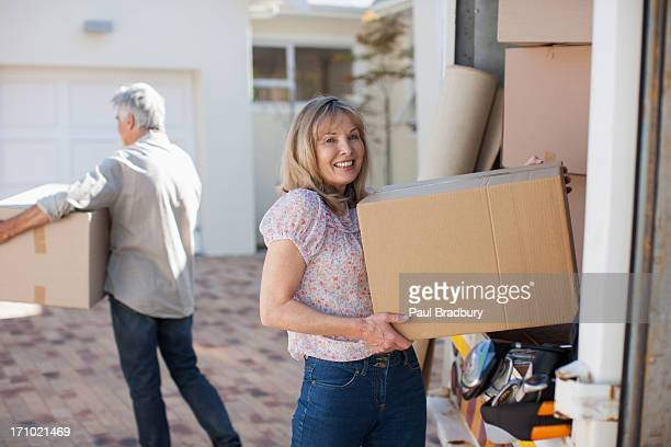Couple carrying boxes from moving van