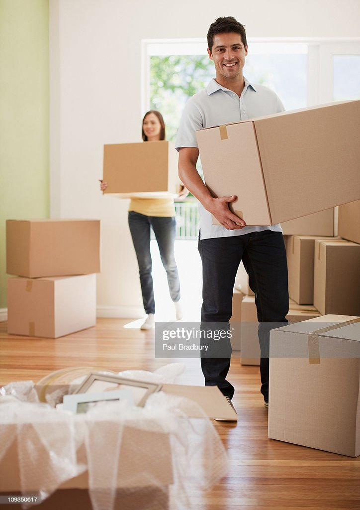 Couple carrying boxes into their new house : Stock Photo