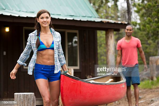 Couple carrying canoe to the lake.