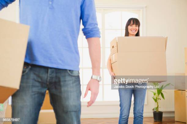 Couple carrying cardboard boxes in new home