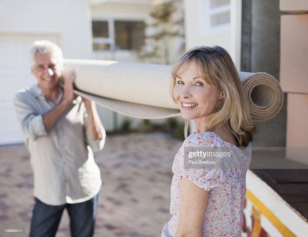 Couple carrying carpet from moving van : Stock Photo