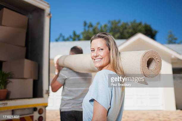 Couple carrying carpet from moving van