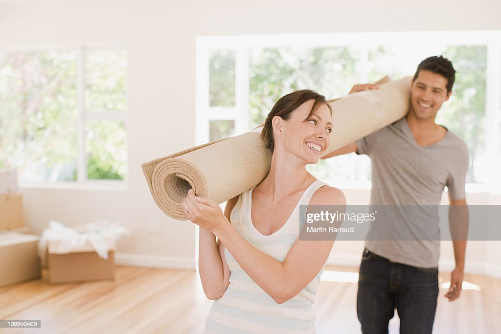 Couple carrying carpet into new house : Stock Photo