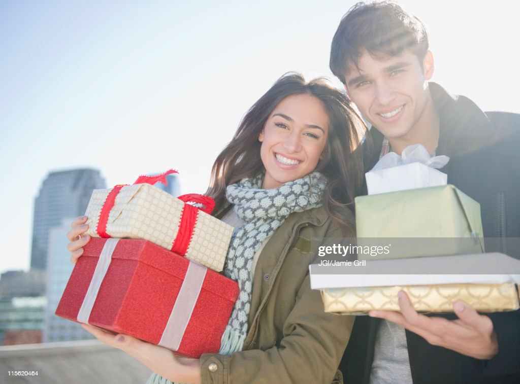 Couple carrying Christmas gifts : Stock Photo
