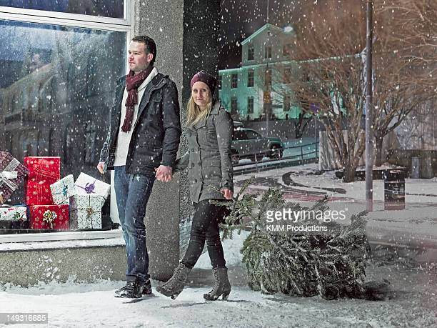 Couple carrying Christmas tree in snow