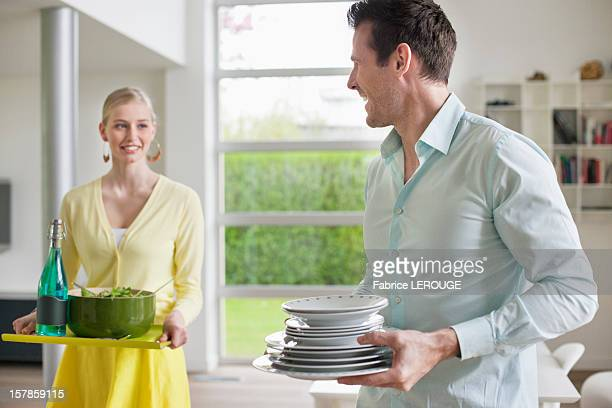 Couple carrying food and plates for serving