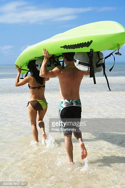 Couple carrying kayak on heads to ocean, rear view