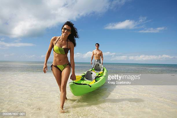 Couple carrying kayak to shore, smiling, portrait