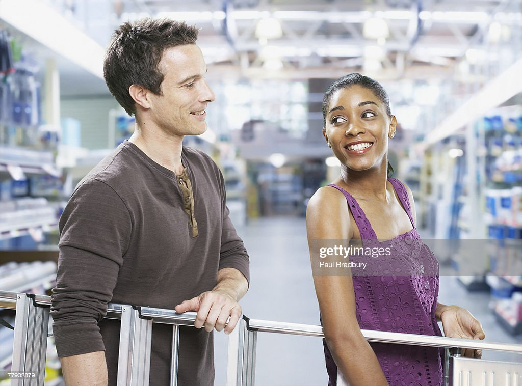 Couple carrying ladder through store : Stock Photo