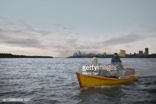 Couple carrying luggage in motorboat, skyline in background : Stock Photo