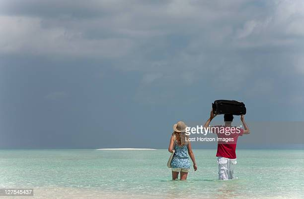 Couple carrying luggage into sea