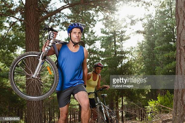 Couple carrying mountain bikes in forest