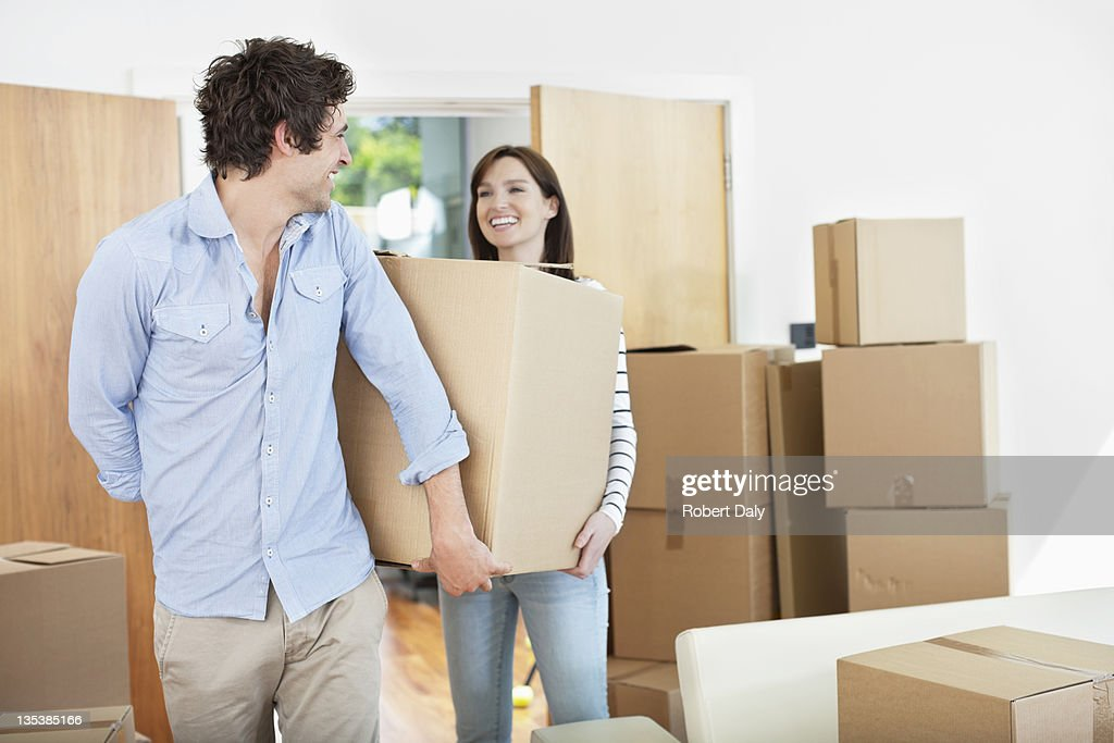 Couple carrying moving boxes into new home : Stock Photo