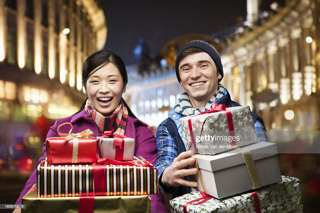 Couple carrying packages in urban retail area. : Stock Photo