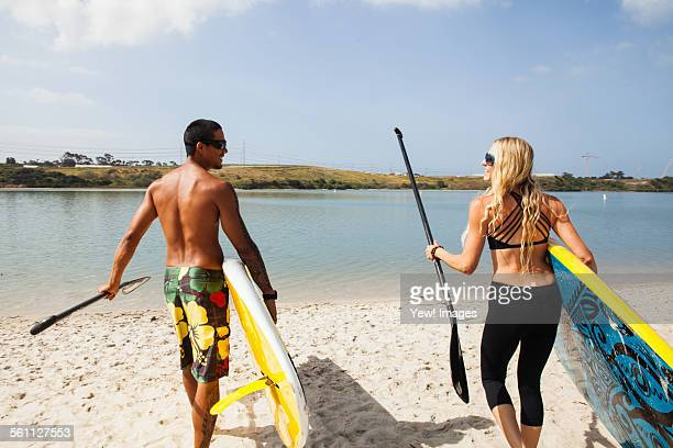 Couple carrying paddleboards on beach, Carlsbad, California, USA