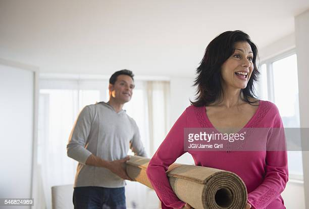 Couple carrying roll of carpet in living room