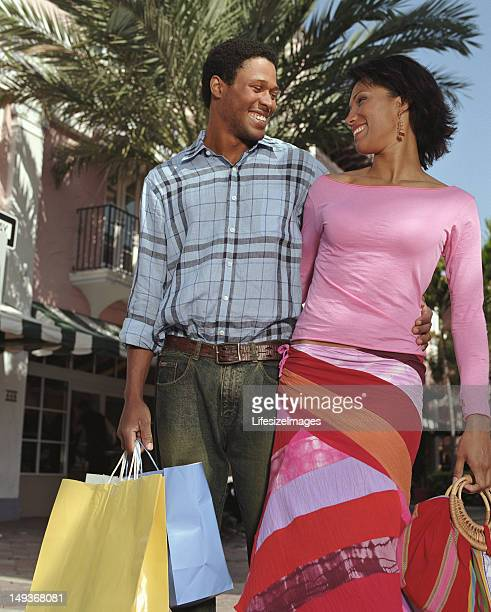 Couple carrying shopping bags embracing outdoors