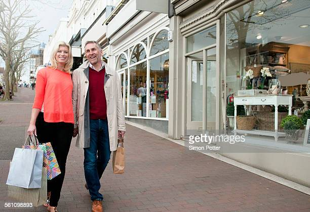 Couple carrying shopping bags on village street