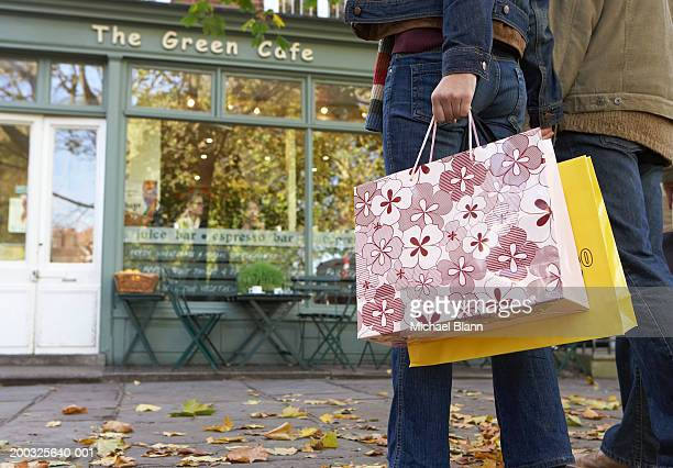 Couple carrying shopping bags, rear view, low section