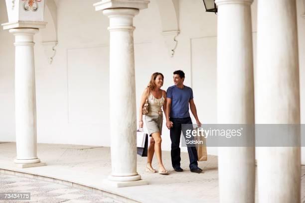 Couple carrying shopping bags through arcade, full length