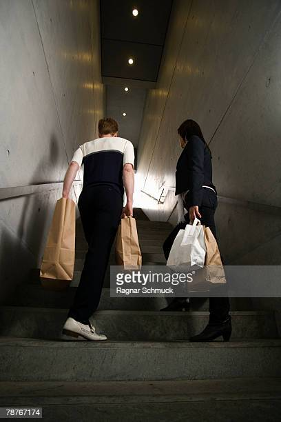 A couple carrying shopping bags up stairs