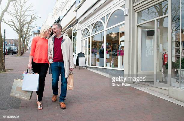 Couple carrying shopping on village street