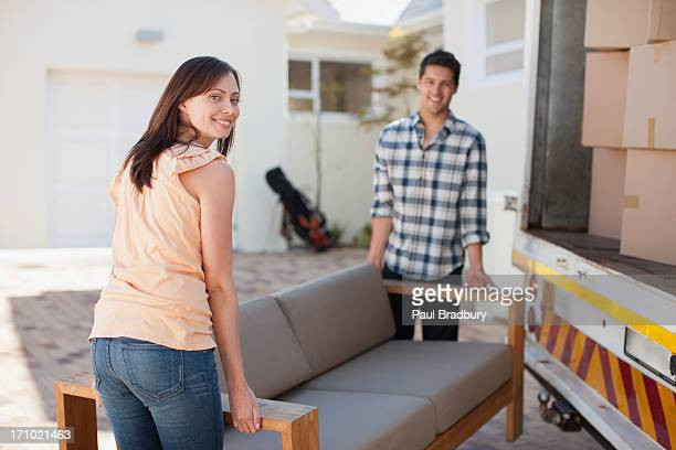 Couple carrying sofa from moving van into new house