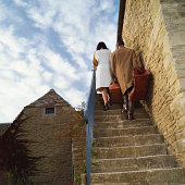 Couple carrying suitcases up steps on side of house, rear view
