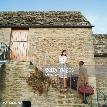 Couple carrying suitcases up steps on side of house, side view