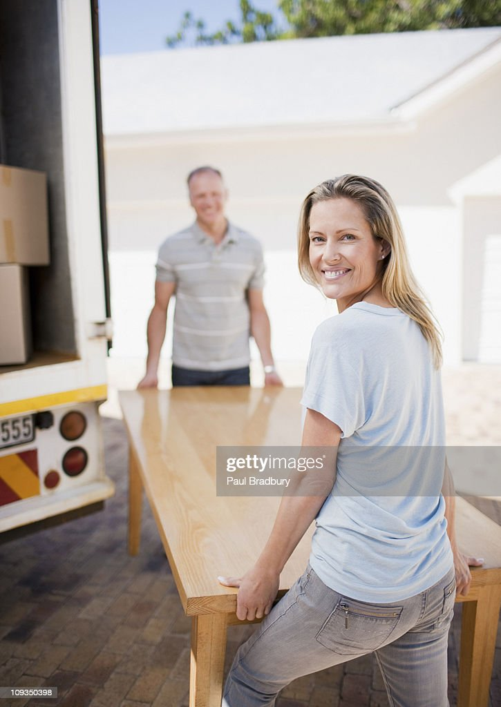 Couple carrying table from moving van : Stock Photo