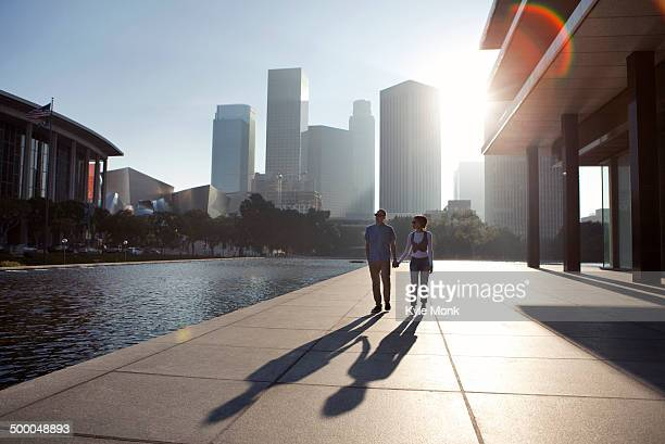 Couple casting shadows on urban waterfront
