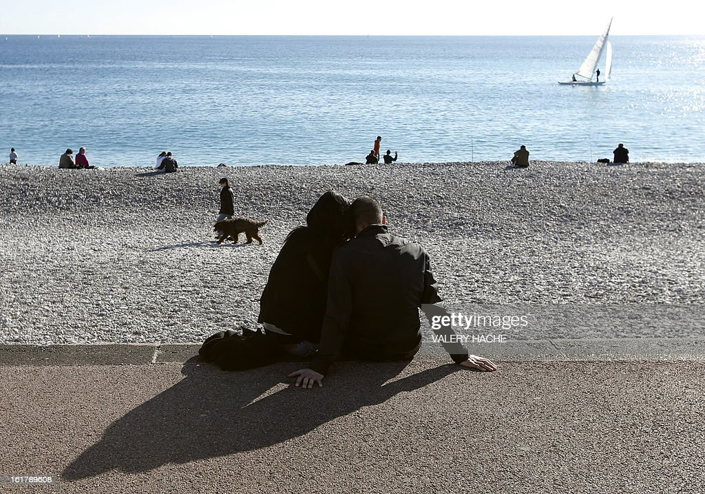 A couple catch some rays of sun on the Mediterranean sea on February 16, 2013 in the southeastern French city of Nice. AFP PHOTO / VALERY HACHE