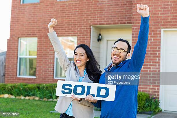 Couple celebrates in front of new home