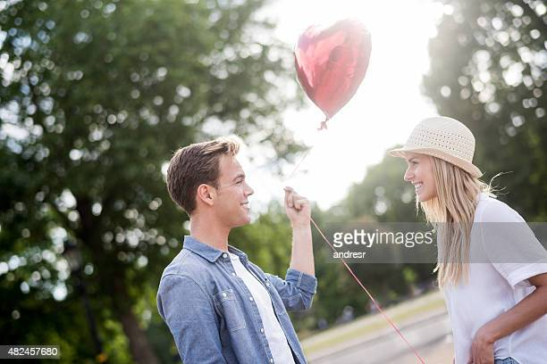 Couple celebrating an anniversary and holding a heart shaped bal