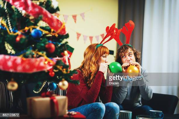Couple celebrating Christmas and blowing balloons