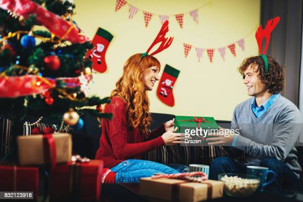 Couple celebrating Christmas and exchanging gifts