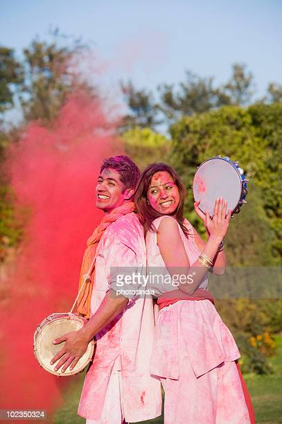 Couple celebrating Holi with colors and musical instruments