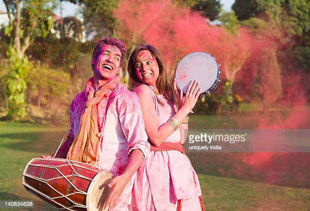 Couple celebrating Holi with musical instruments in a garden