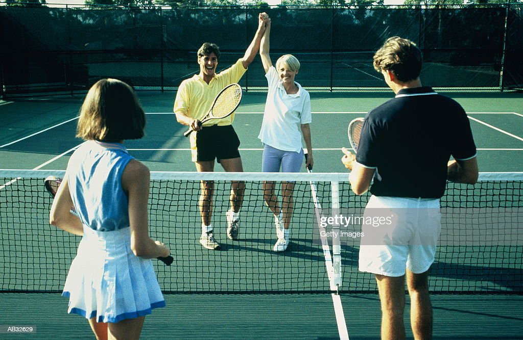 Couple celebrating win in tennis match : Stock Photo