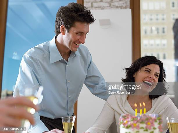 Couple celebrating with birthday cake and champagne