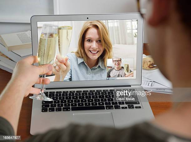Couple celebrating with Champagne over Skype.