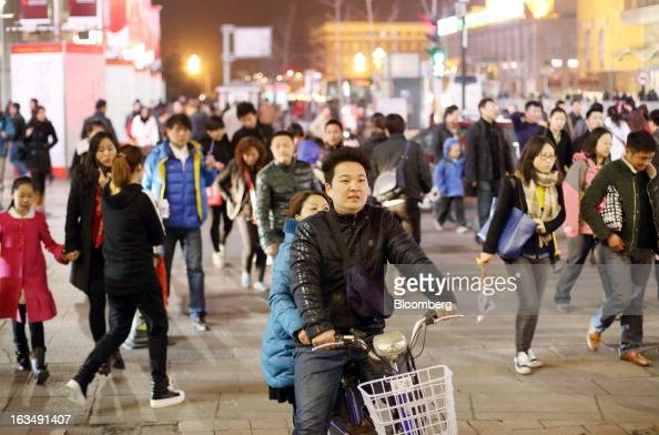 A couple center ride a bicycle as pedestrians walk through the Wangfujing shopping district of Beijing China on Sunday March 10 2013 China's...